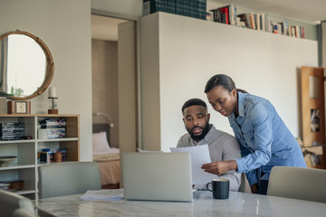 Young African American couple doing their online banking at home