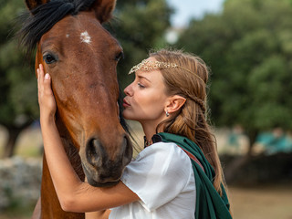 Blonde girl with blue eyes and makeup with elf in the field with a brown horse and a green cape.