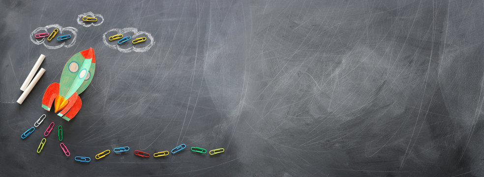 education. Back to school concept. rocket cut from paper and painted over blackboard background. top view, flat lay. banner