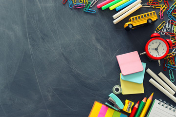education and back to school concept. stationery and bus over classroom blackboard. top view, flat lay