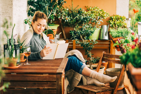 Young beautiful woman relaxing on cozy balcony, reading a book, wearing warm knitted pullover, glass of wine on wooden table