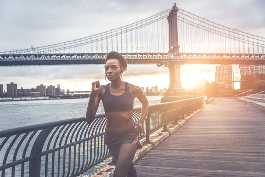 Athlete woman training in the morning at sunrise in New york city, Brooklyn in the background