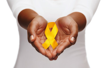 healthcare, charity and medicine concept - close up of woman cupped hands holding yellow gold childhood cancer awareness ribbon