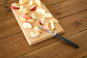fruits, food cooking and eating concept - sliced apples and kitchen knife on wooden cutting board