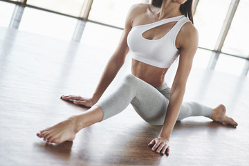 Cropped picture. European young brunette doing yoga in the room with big windows
