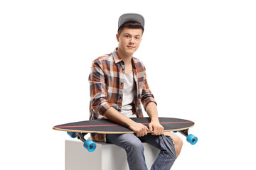 Male teenager sitting with a longboard
