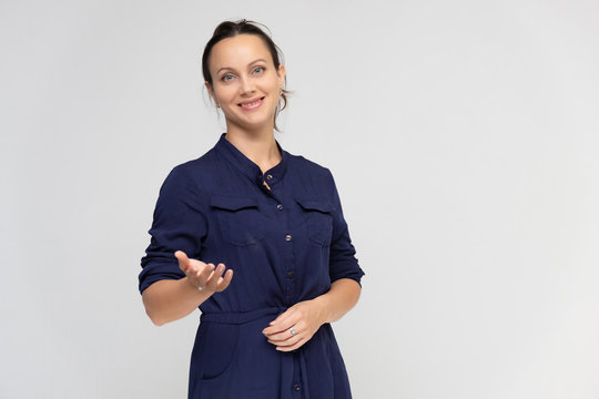 Portrait of a young pretty brunette woman of 30 years old in a simple plain blue dress with dark hair. Standing right in front of the camera, talking, showing hands, demonstrating emotions.