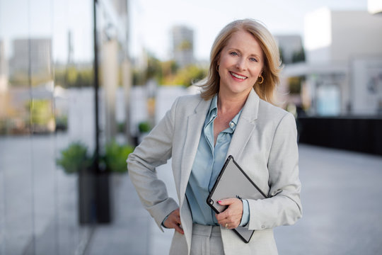 Mature business executive professional woman portrait, in suit outside of office in business district