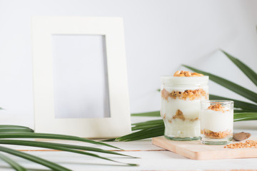 Healthy meal made of granola in glass, Yogurt and cornflakes Decorate food with Cashew Nut beside has Ornamental plants and picture frame setting on white wooden table, healthy care concept