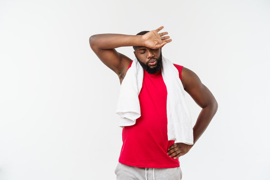 Close up shot of a sad tired African American man in sportswear wiping his face with a white towel, on white background
