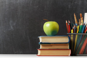 Set for the student. A stack of books, an apple, pencils against the background of the school black board. The concept of education. Copy space
