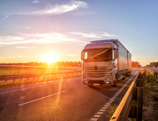 Modern wagon truck transports cargo against the backdrop of a sunset. The concept of truck drivers in the field of freight and logistics, copy space
