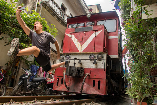Man with mobile phone makes dangerously selfie photo in front of moving train. An undisciplined tourist in the popular Hanoi railway street, Vietnam.