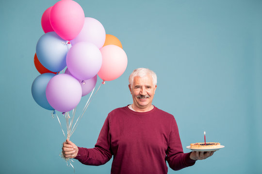 Happy senior man with bunch of balloons and birthday cake