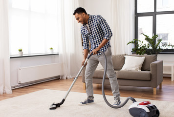 household and cleaning concept - indian man with vacuum cleaner at home