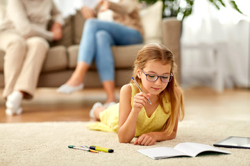 education, school and learning concept - student girl lying on floor and writing to notebook at home