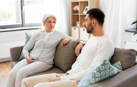 family, generation and people concept - happy smiling senior mother talking to adult son at home
