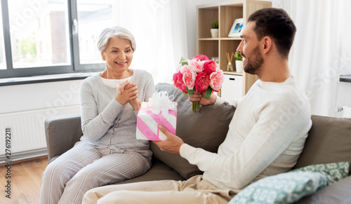 family, mother's day and birthday concept - smiling adult son giving present and flowers to his senior mother at home