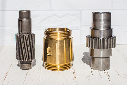 Shaft gear with oblique tooth with a nitrated surface, with a straight tooth and a conical sleeve on a white wooden background.