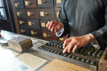 Tradiotional Chinese medicine practitioner counting price of herbs on abacus