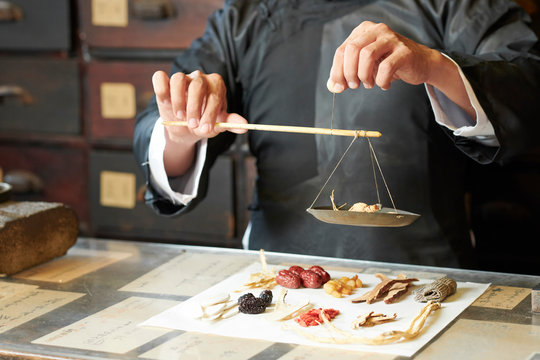 Close-up image of traditional Chinese medicine practitioner using special scales to weight dry plant roots for treatment
