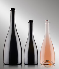 three champagne bottles on grey background