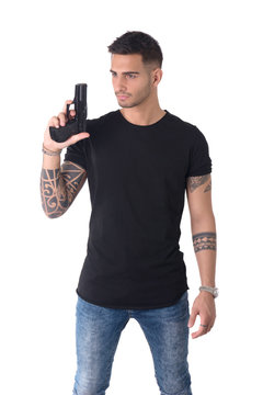 Young handsome man holding gun, wearing black t-shirt, isolated on white background