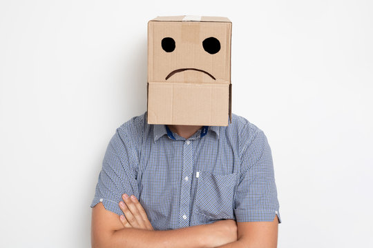 a man with a cardboard box on his head, a sad smiley