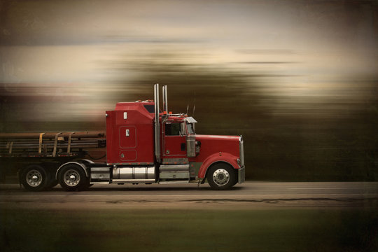 Bright red modern big rig semi truck and trailer in motion on a highway