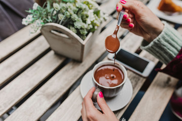 Papiers peints Chocolat young unrecognizable caucasian woman enjoying a hot chocolate in a terrace with friends. Lifestyle outdoors
