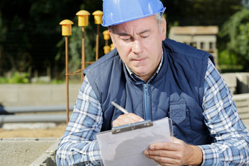 mature construction manager writing report at construction site