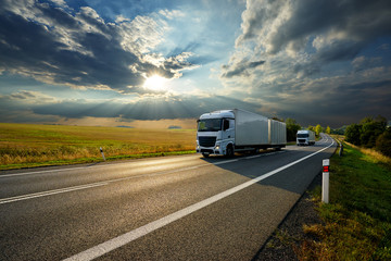 Fotobehang - Two white trucks driving on the asphalt road in rural landscape at sunset with dramatic clouds