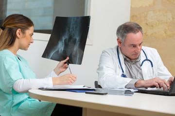practitioner examining pelvic xray
