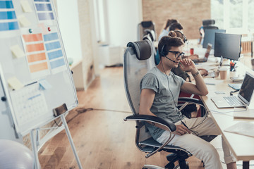 Concentrated guy in glasses is working in the call center
