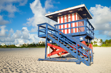 Summer beach travel scene with classic red, white, and blue American flag themed lifeguard tower in Miami, Florida, USA