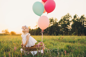 Baby girl in wicker basket with balloons on nature at summer