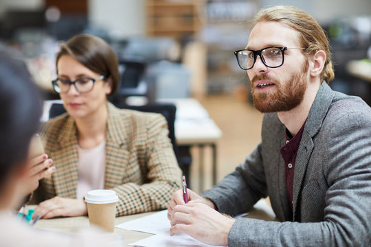 Portrait of contemporary bearded businessman talking to colleagues during meeting in office, copy space