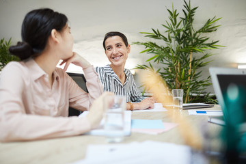 Portrait of mature woman smiling happily looking at colleague in business meeting, copy space