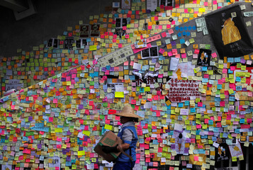 A worker walks past post-it notes scribbled with messages, left behind by protesters on the walls of the Legislative Council, a day after protesters broke into the building, in Hong Kong