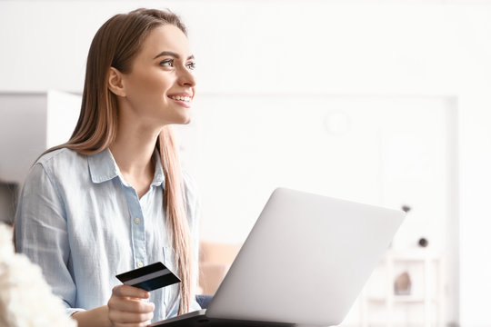 Young woman with credit card shopping online at home