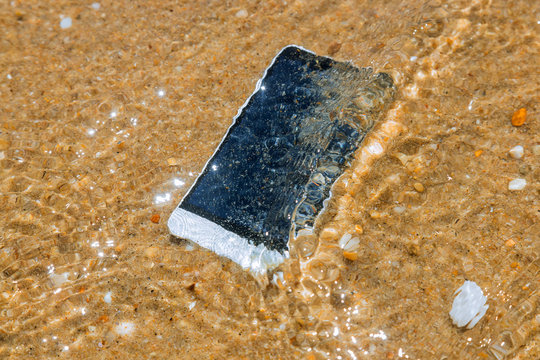 Smart phone with weather on a sandy beach