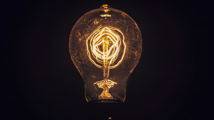 Vintage Filament Light Bulb Up Close Isolated on Black Background Energy Idea Concept