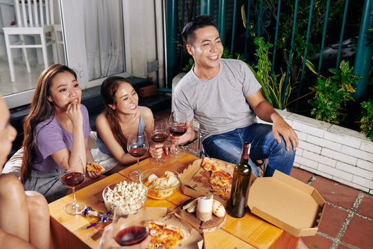 Group of young people enjoying movie night with snack and drinks in backyard