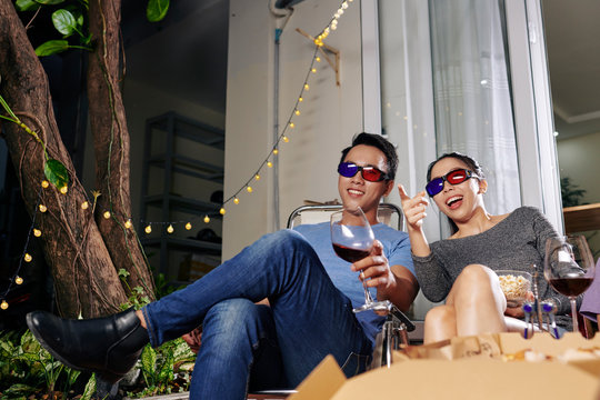 Cheerful young Asian couple in 3D glasses drinking wine and watching comedy movie via projector in backyard
