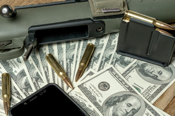 Rifle, magazine and cartridges on money. Concept for crime, contract killing, paid assassin, terrorism, war, global arms trade, weapons sale. Illegal hunting, poaching. Black screen smartphone