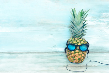 Ripe pineapple with blue mirror sunglasses and headphones in front of a blue wooden rustic background. Wall mural