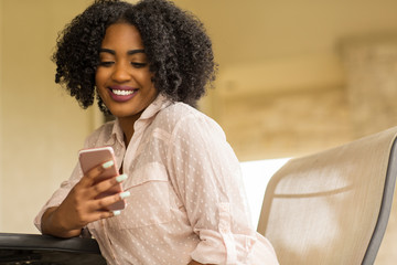 Happy African American woman texting and talking.