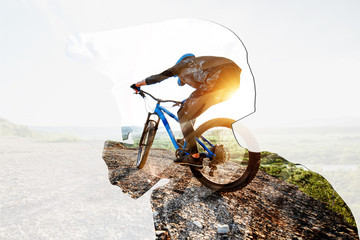 Double exposure of a man in protective helmet and professional cyclist riding on the mountains. Concept of a freeride and off road cycling Fototapete