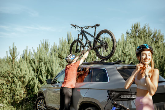 Young couple preparing for the bicycle riding, picking up mountain bicycle from the car trunk during the summer vacations in the forest