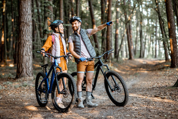 Young couple dressed casually standing together with mountain bicycles, traveling in the forest...
